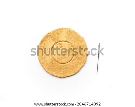 Korean Dalgona or Ppopgi candy on white background. Honeycomb toffee sugar candy with circle shape and needle to play breaking candy game  Royalty-Free Stock Photo #2046714092