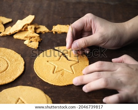 Playing Korean Dalgona or Ppopgi candy game with needle. Honeycomb toffee sugar candy with star shape. Royalty-Free Stock Photo #2046739817