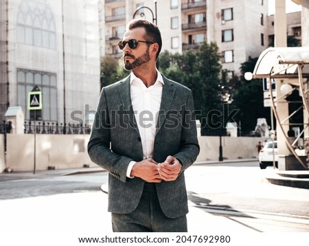 Portrait of handsome confident stylish hipster lambersexual model.Sexy modern man dressed in elegant suit. Fashion male posing in the street background in Europe city at sunset. In sunglasses Royalty-Free Stock Photo #2047692980