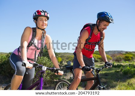 Active couple cycling in the countryside on a sunny day #204793192