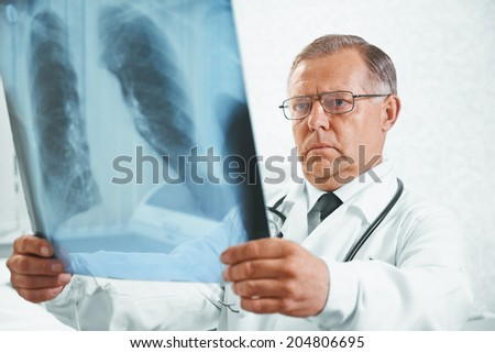 Older man doctor examines x-ray image of lungs in a clinic