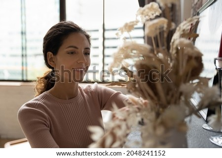Close up of happy young Caucasian woman take care of flowers decorate cozy modern home or apartment. Smiling millennial female decorate engaged in interior design of new house. Rental concept. Royalty-Free Stock Photo #2048241152