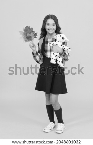 Childhood is full of learning. Happy little schoolgirl hold childhood toy and autumn leaves. Small child back to school yellow background. Childhood games kids play. Childhood fun and learn Royalty-Free Stock Photo #2048601032