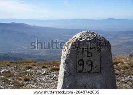 Boundary pyramid on the border between Bulgaria and Greece. View from Slavyanka mountain. Peaks in sunny autumn day. Royalty-Free Stock Photo #2048742035