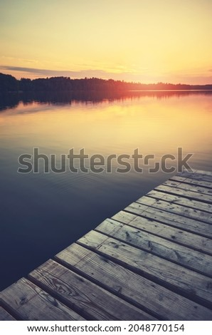 Sunset over still lake, wooden pier in foreground, color toning applied. Royalty-Free Stock Photo #2048770154