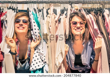 Young beautiful women at weekly cloth market - Best friends sharing free time having fun and shopping in old town on sunny day - Girlfriends enjoying everyday life moments - Looking at camera view Royalty-Free Stock Photo #204877840