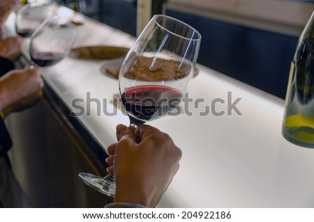 Some people are holding red wine cups in a wine tasting to see the wine transparency #204922186