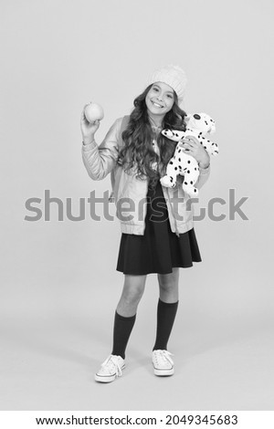 Childhood games kid plays. Happy girl hold toy and apple. Healthy school snack. Happy childhood. Childhood fun. Care of childhood. International childrens day. Back to school. Autumn season Royalty-Free Stock Photo #2049345683