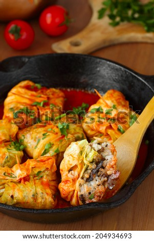 Stuffed cabbage rolls with rice and mushrooms in tomato sauce. Dolma, sarma, or golubtsy - traditional dish of many countries #204934693