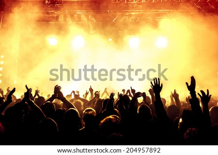 silhouettes of concert crowd in front of bright stage lights Royalty-Free Stock Photo #204957892