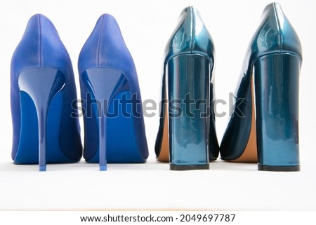 Two pairs of blue women's shoes. High-heeled shoes. One pair of thin heels, stiletto heels. The second pair has a stable wide heel. Fashionable stylish shoes Royalty-Free Stock Photo #2049697787