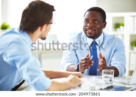 Image of two young businessmen interacting at meeting in office Royalty-Free Stock Photo #204973861