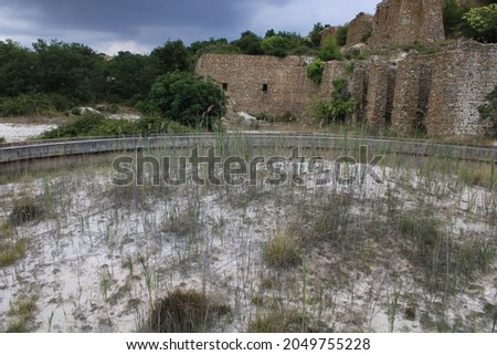 Old destroyed buildings at the mines of Vavdos, overtaken by nature Royalty-Free Stock Photo #2049755228