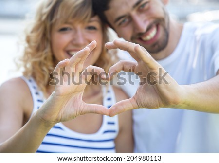 Happy love couple outside showing heart with fingers #204980113