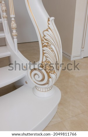 wooden staircase with carved balusters in light colors with a gold print Royalty-Free Stock Photo #2049811766