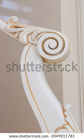 wooden staircase with carved balusters in light colors with a gold print Royalty-Free Stock Photo #2049811781