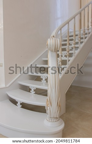 wooden staircase with carved balusters in light colors with a gold print Royalty-Free Stock Photo #2049811784