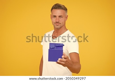 Happy birthday darling. Man happy face celebrate valentines day. Little gift. Gift for girlfriend. Romantic gift. Mature guy hold present box yellow background. Love romantic feelings concept Royalty-Free Stock Photo #2050349297