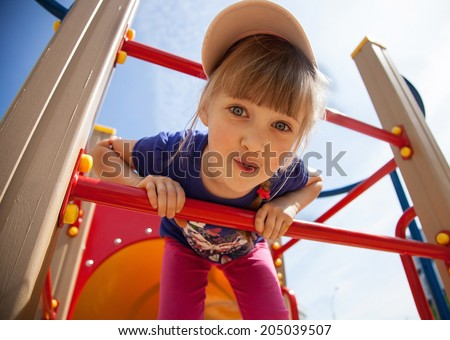 Active little girl on playground Royalty-Free Stock Photo #205039507