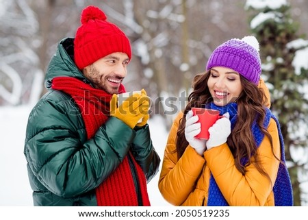 Photo of charming pretty marriage couple wear windbreakers smiling drinking coffee walking snowy weather outside park Royalty-Free Stock Photo #2050519235