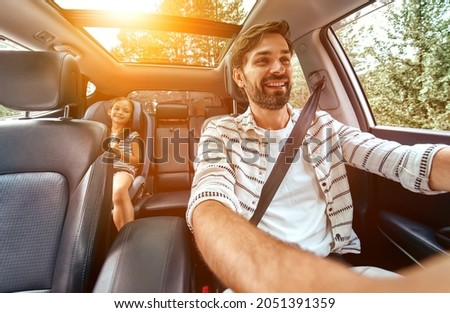 Child cute girl in a car seat protected by seat belts with her dad going in the car for the weekend. Leisure, travel, tourism. Royalty-Free Stock Photo #2051391359