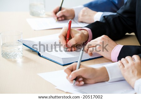 Hands taking notes, focus is on the pen #20517002