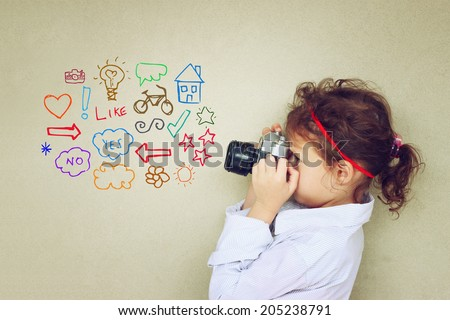 Concept of cute kid looking through vintage camera viewfinder and various drawings
