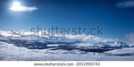 Very scenic panorama view at Scandinavian Mountains, ski slope with lot of traces. No people yet, Sunny day , much snow and blue skies with fluffy clouds, strong Sun Royalty-Free Stock Photo #2052900743