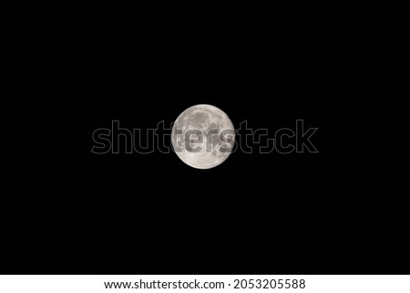 Bright white full moon on dark night sky. Mystic nighttime black sky with moon, dark tranquility. Perigee night, lunar closest to Earth Royalty-Free Stock Photo #2053205588