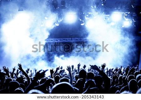 silhouettes of concert crowd in front of bright stage lights #205343143