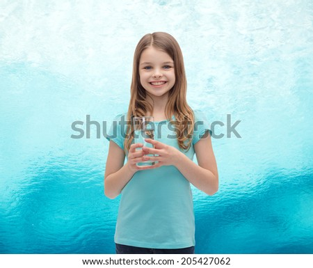 health and beauty concept - smiling little girl with glass of water #205427062