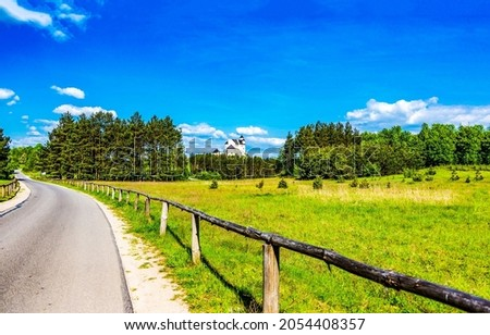 Fencing along a rural road. Rural road fence. Fencing rural road. Countryside road fence Royalty-Free Stock Photo #2054408357