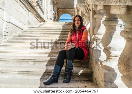 Young brunette woman sitting on a white ladder with balusters. The girl travels to beautiful palaces. Stairs with balusters in the historic courtyard of the building. Royalty-Free Stock Photo #2054464967