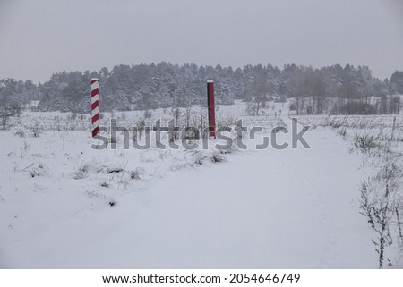 Boundary pillars of Belarus and Poland on the border in a winter field Royalty-Free Stock Photo #2054646749