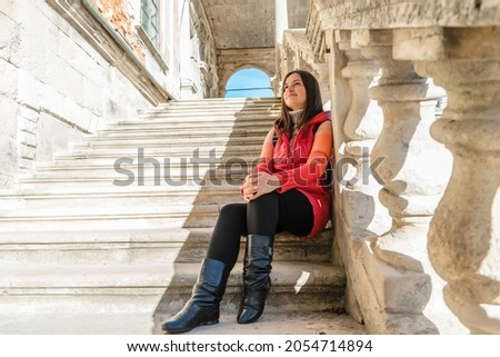 Young brunette woman sitting on a white ladder with balusters. The girl travels to beautiful palaces. Stairs with balusters in the historic courtyard of the building. Royalty-Free Stock Photo #2054714894