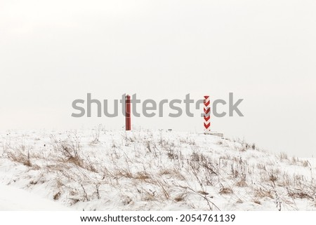 Boundary pillars of Belarus and Poland on the border in a winter field Royalty-Free Stock Photo #2054761139