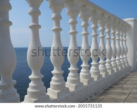 A balustrade with a view of the sea, sky and horizon, a fence consisting of a row of figured baluster posts, connected from above by a railing or a horizontal beam. Railing from curly white posts. Royalty-Free Stock Photo #2055731135