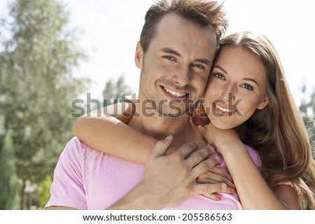 Portrait of beautiful young woman embracing man in park #205586563