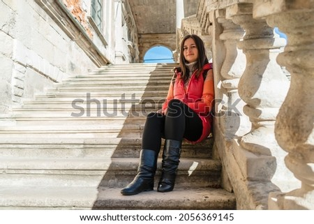 Young brunette woman sitting on a white ladder with balusters. The girl travels to beautiful palaces. Stairs with balusters in the historic courtyard of the building. Royalty-Free Stock Photo #2056369145