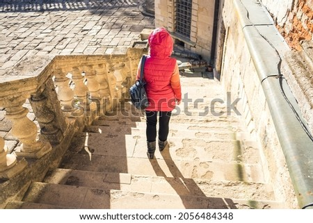 The girl with a backpack goes down the white stairs with balusters. Woman in a jacket on the white stairs in a beautiful bright palace. Courtyard of an ancient castle. Royalty-Free Stock Photo #2056484348