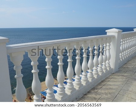Anapa, Russia 23 August 2021. Balustrade overlooking the sea, sky and horizon, a fence consisting of a row of curly posts of balusters connected by a horizontal beam. Railing from curly white posts. Royalty-Free Stock Photo #2056563569