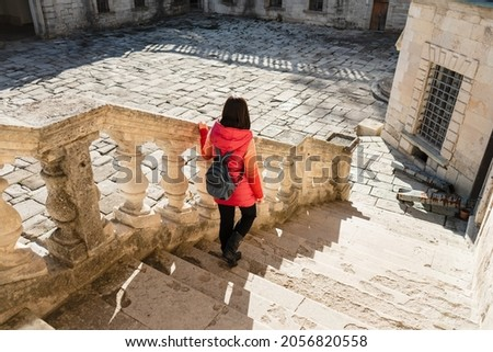 The girl with a backpack goes down the white stairs with balusters. Woman in a jacket on the white stairs in a beautiful bright palace. Courtyard of an ancient castle. Royalty-Free Stock Photo #2056820558