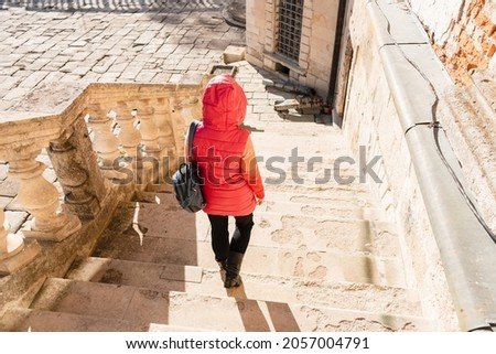 The girl with a backpack goes down the white stairs with balusters. Woman in a jacket on the white stairs in a beautiful bright palace. Courtyard of an ancient castle. Royalty-Free Stock Photo #2057004791