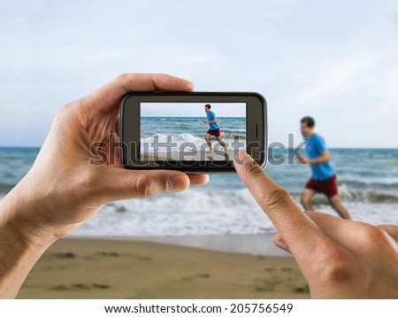 man taking a picture with your mobile phone a one man running for joy on the beach