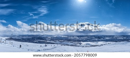 Very scenic panorama view at blue sky above  Scandinavian Mountains, ski lift. Sunny day, much snow and blue skies with fluffy clouds, small snowflakes shine against Sun Royalty-Free Stock Photo #2057798009