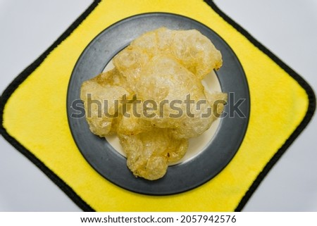 Indonesian original snack skin crackers, delicious, crunchy, savory on a yellow white background. Royalty-Free Stock Photo #2057942576