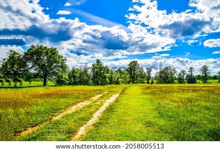 Thick clouds over a rural road through a field. Rural road landscape. Country road view Royalty-Free Stock Photo #2058005513