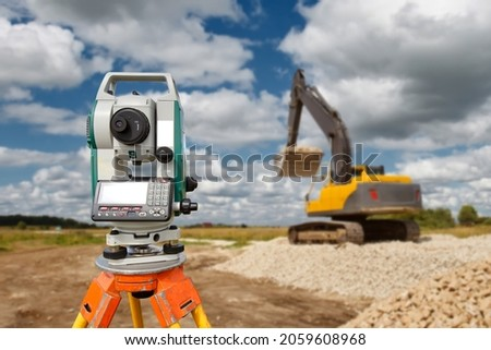 Geodetic device at construction site. Optical level at construction site. Excavator on stone embankments. Equipment for work as surveyor. Optical theodelite on tripod Device for creating geodetic map Royalty-Free Stock Photo #2059608968