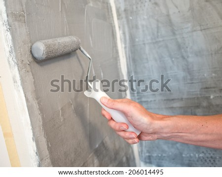 Painting a wall with a roller #206014495