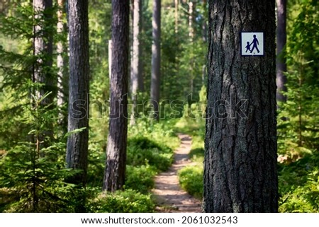 Footpath in green forest with footpath symbol sign attached to tree trunk. Royalty-Free Stock Photo #2061032543